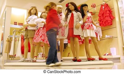 Girl stands near dummies in red dresses in shopping center, time lapse
