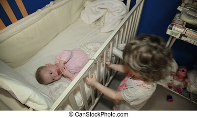Girl stands near the bed with their baby sister.