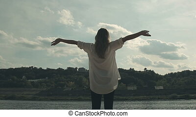 girl stands near the river and joyfully lifts hands