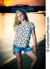 girl stands near the water