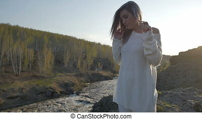 Girl stands on a rock on a background of the river