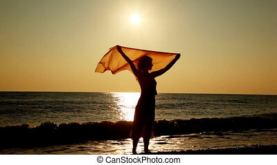 Girl stands on beach and holds over her head scarf fluttering in breeze