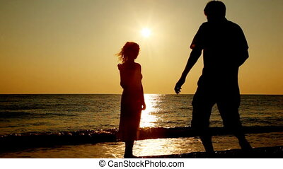 Girl stands on beach, boy comes, takes her hands, silhouettes at sunset, part1