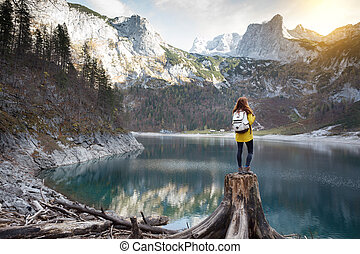 girl stands on the shore of a mountain lake