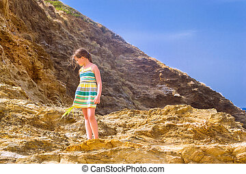 Girl stands on top of cliff. Bali, Crete - Sweet girl stands...