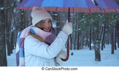 girl stands under the umbrella and twists it, and pour around snow