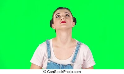 Girl stands waiting on a green screen. Slow motion