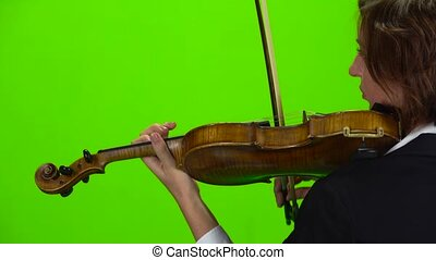 Girl stands with her back and plays the violin. Green...