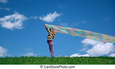 Girl stands with rainbow fabric in hands