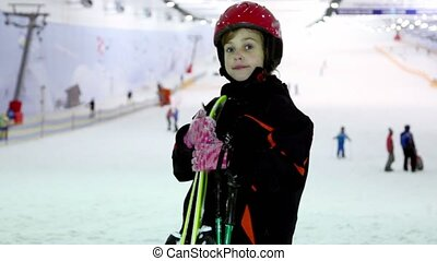 girl stands with ski at background of snow slope and ropeway...
