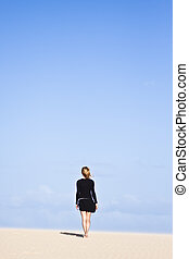 Beautiful girl standing on the sand dune and looking in the distance.