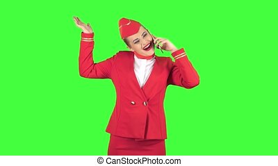 Girl stewardess is talking on the phone and is happy. Green Screen