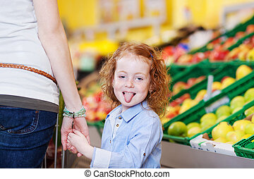 Girl Sticking Out Tongue While Holding Mother's Hand In Grocery