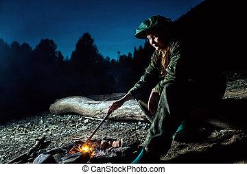 Girl stirs coals around the campfire