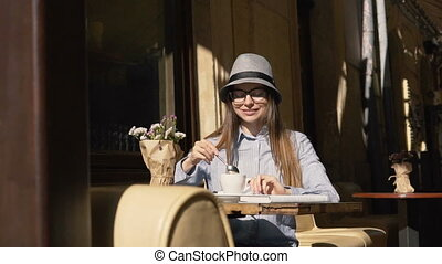 Girl Stirs Coffee in Outdoor Cafe - Smiling girl, in grey...