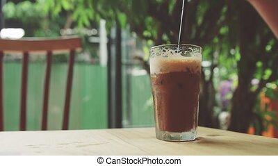 girl stirs iced coffee
