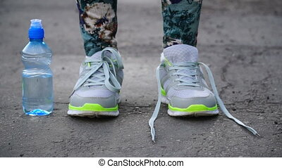 girl stopped running to tie the laces on running shoes. ...