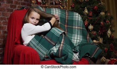 Girl straightens her hair sitting in a chair near a Christmas tree