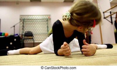 Girl stretches under surveillance of ballet teacher