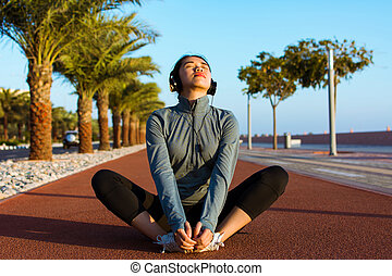 Girl stretching on a running track with headphones