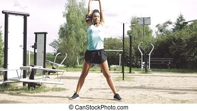 Girl stretching on sports ground - Fit young woman in...