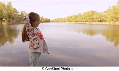 Girl stroking her hair and looking at the lake - Little girl...