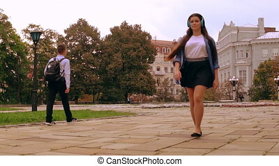 girl stroll in city - caucasian young woman listening music...
