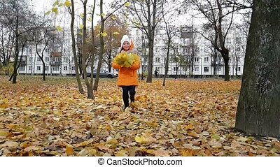 Girl student is playing with leaves in autumn Park