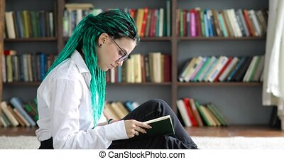 Young girl student with dreads hair in glasses reading book in library sitting on floor, side view. Girl with green dreadlocks learns literature at University College School campus. Studying concept.