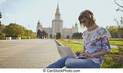 Girl student working with a laptop on a square on the background of Lomonosov Moscow State University.