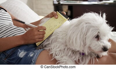 Girl Studying For School Homework With Dog On Legs