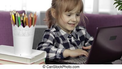 Pretty preschool girl distance online learning at home. Focused cute kid listening audio lesson studying at table using digital laptop computer, doing homework. Children remote education on quarantine