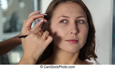 Girl Stylist Working in a Beauty Studio. Make-up For a Beautiful girl.