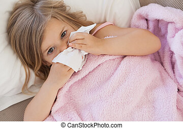Girl suffering from cold as she lie
