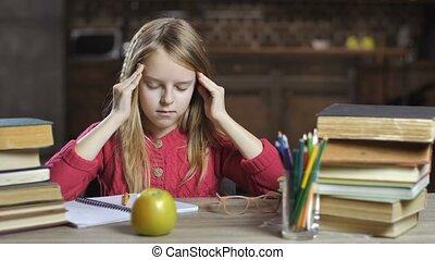 Girl suffering from headache while doing homework -...
