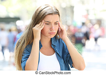 Girl suffering head ache in the street
