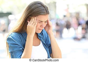 Girl suffering migraine in the street