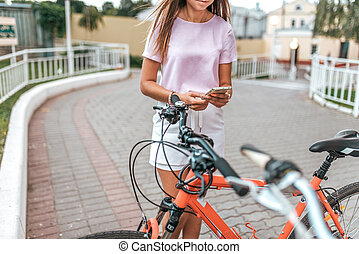 Girl summer stands bicycle, activates application buying rental bicycle in parking lot, in hands of phone. Online selection of route on map in the city. Cycling on weekend. Route map on phone.