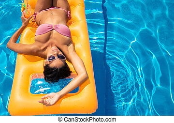 Girl sunbathing on air mattress - Young girl sunbathing on...