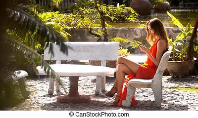 Girl Surfs Internet on Phone in Pictorial Garden - closeup...