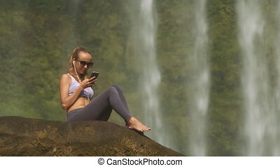 Girl Surfs Internet Sitting on Stone by Waterfall