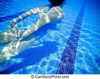 Girl swimming underwater in a swimming pool
