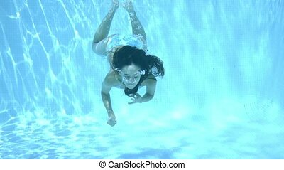 Girl swimming underwater in a swimming pool through...