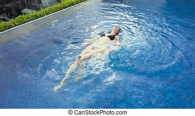 Girl swims in the pool. Aerial view