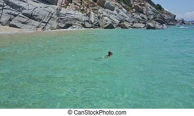 Girl Swims in Tranquil Azure Ocean near Rocky Beach - girl...