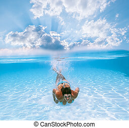 Girl swims under water in the pool