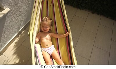 Girl swinging in hammock - Funny little girl wrapping in...