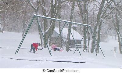 Girl Swinging in Snow - Boy pushing girl on swing during...