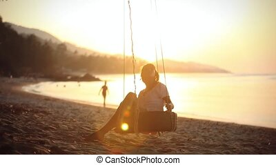 Girl swinging on a wheel with sunset near the beach