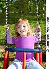 girl swinging on swing happy in meadow grass park